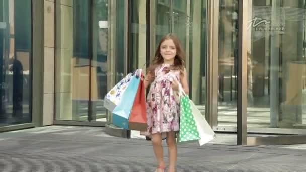 Roztomilá holčička s nákupníma taškama z dílny, radost nakupovat