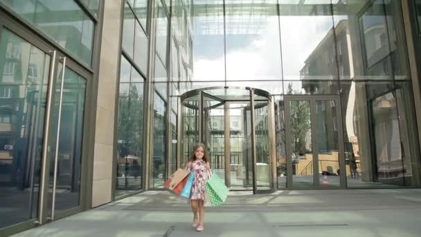 Aranyos kislány, a bevásárló szatyrok sétál ki a boltból, Boldog vásárlás