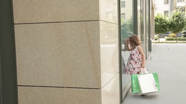 Malá holčička se dívá na okně poblíž nákupního centra