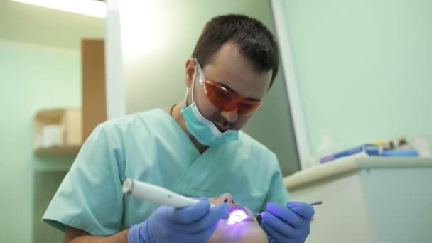 Dentist using dental curing UV lamp on teeth of patient