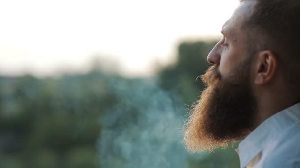 Handsome bearded man, stylish hipster male smoking cigarette outdoor