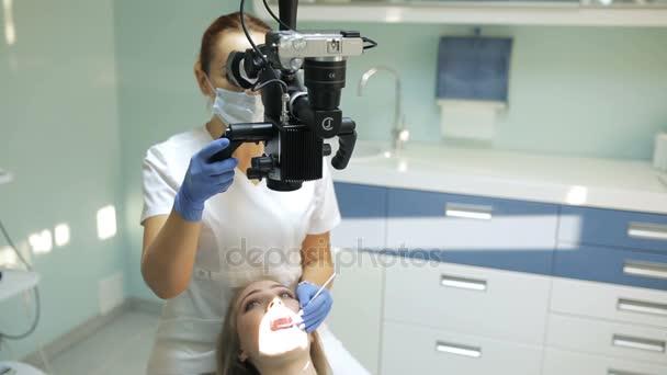 Zubař pomocí dentální mikroskop v zubním lékařství pro fungování pacienta žena