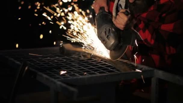 Mladý muž ve svářečských brýlí funguje jednotka rozbrušovačka na čerpací stanici