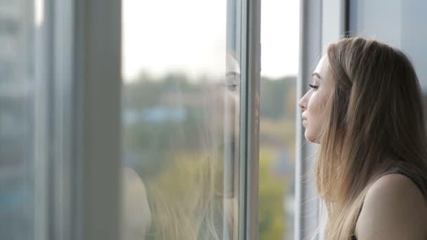 Dívka, dýchat čerstvý vzduch z otevřeného okna