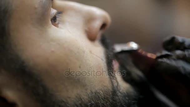 Barber oholí vousy klienta zastřihovačem