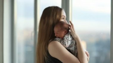 Young mother with a newborn daughter standing near the window