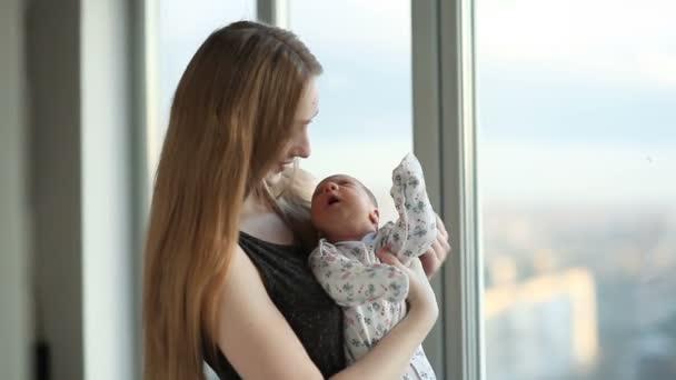Mladá matka s novorozenou dceru, stojící u okna