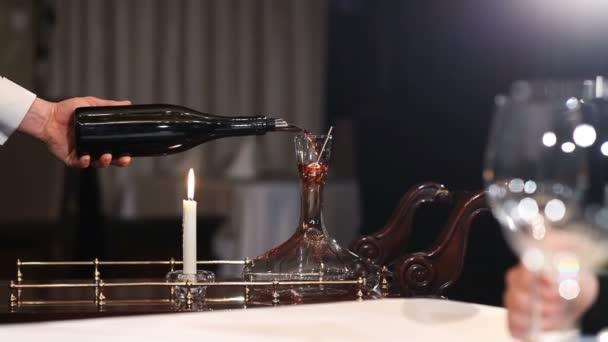 sommelier nalévání červeného vína do karafy