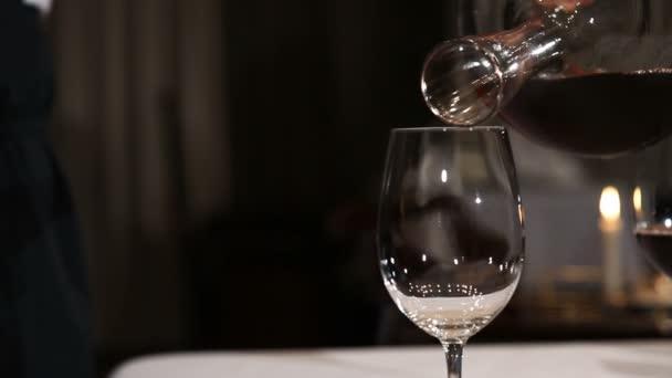 Sommelier nalévá červené víno do sklenice z karafy