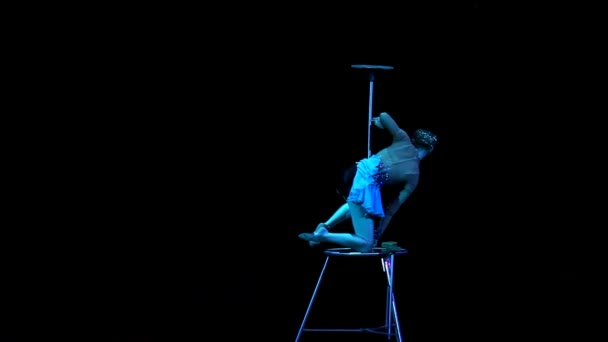 Young flexible acrobat girl executes tricks on a cube in circus