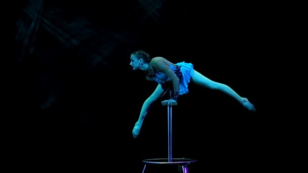 Young flexible acrobat girl doing equilibre balance on a cube in circus