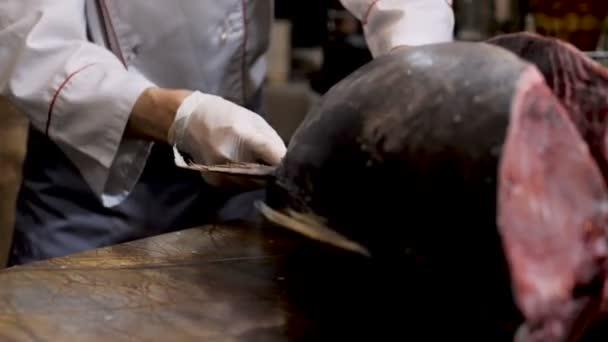 Šéf krájí velkou tuňáka ryby v restauraci