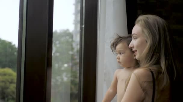 Batole dívka s maminkou stojící na pozadí panoramatického okna