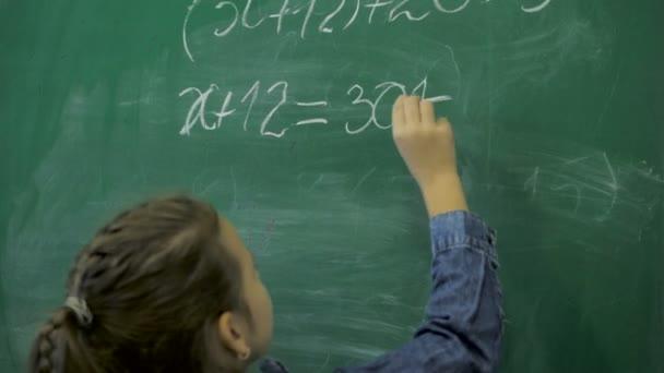Általános iskola. Kis iskolás lány számokat ír a zöld krétával táblára az osztályteremben.