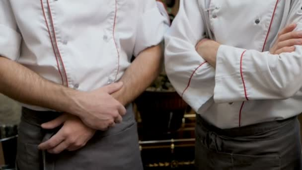 Kuchaři v zástěrách stojící na briefingu v jídelně