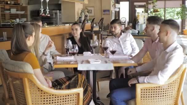 Genç arkadaşlar restoranda eğlenmek kırmızı şarap içiyor. Gençlik dostluk konsepti