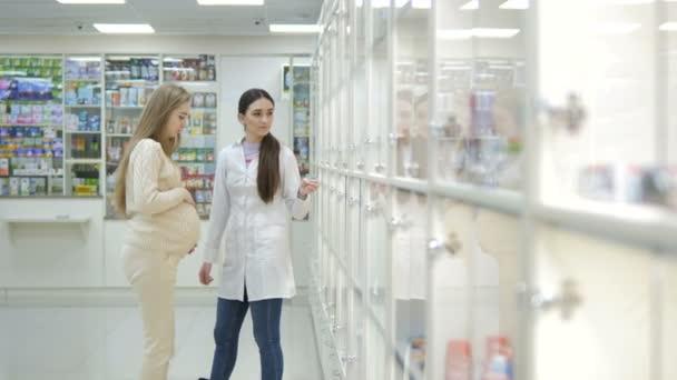 Junges Apothekermädchen hilft schwangeren Kunden bei der Wahl der Behandlung. Pharmazeutisches Filialkonzept