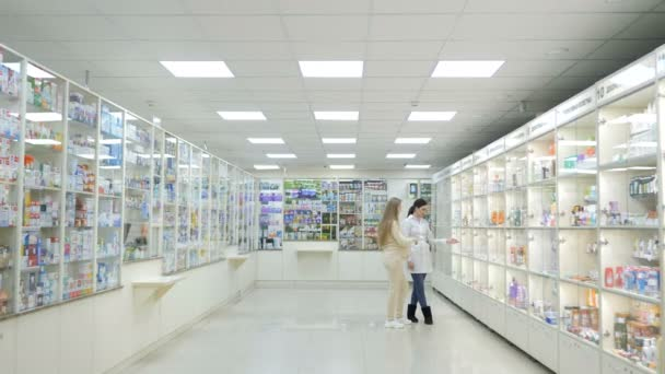Young girl pharmacist helping the pregnant customer to choose the treatment. Pharmaceutical store concept