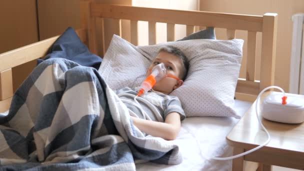 Kleiner Junge wird mit einem Vernebler behandelt, Husten. Kleiner Junge macht therapeutische Inhalation mit einem Vernebler