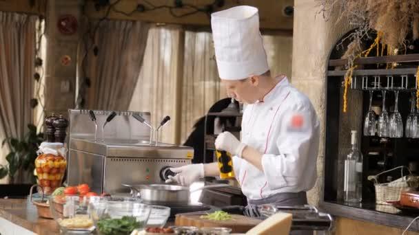 Kuchař smažení česnek v olivovém oleji v restauraci