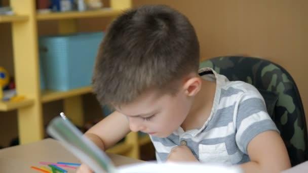 Otthoni tanulás. A fiú otthon csinálja a házi feladatát a karantén alatt.