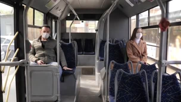 Young man and woman with protective mask traveling in the public transport by bus