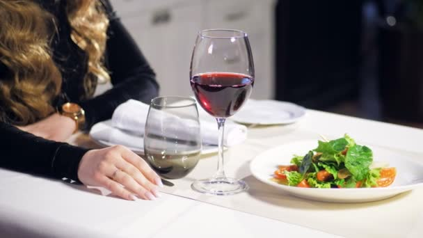 Krásná dívka se sklenkou vína v restauraci
