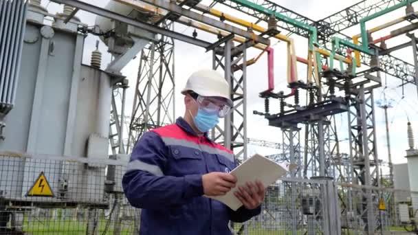 Inženýr v ochranné masce proti Covid-19 pracující na kontrolním zařízení v průmyslu. Energetika