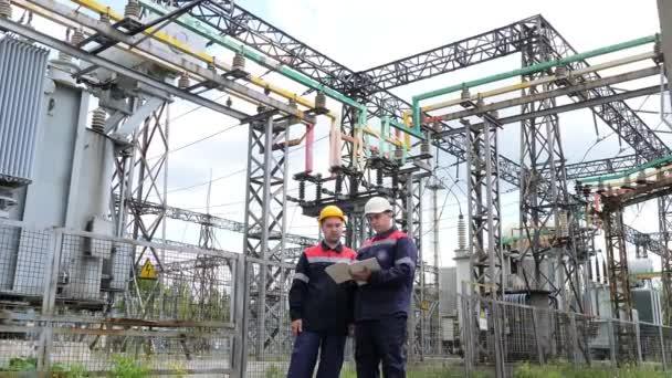 Zwei Ingenieure arbeiten an der Überprüfung und Wartung der Ausrüstung des Umspannwerks. Energietechnik