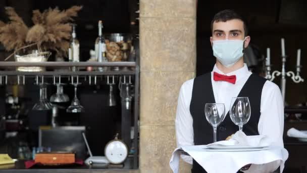 Číšník v ochranné masce obsluhuje stůl v restauraci.