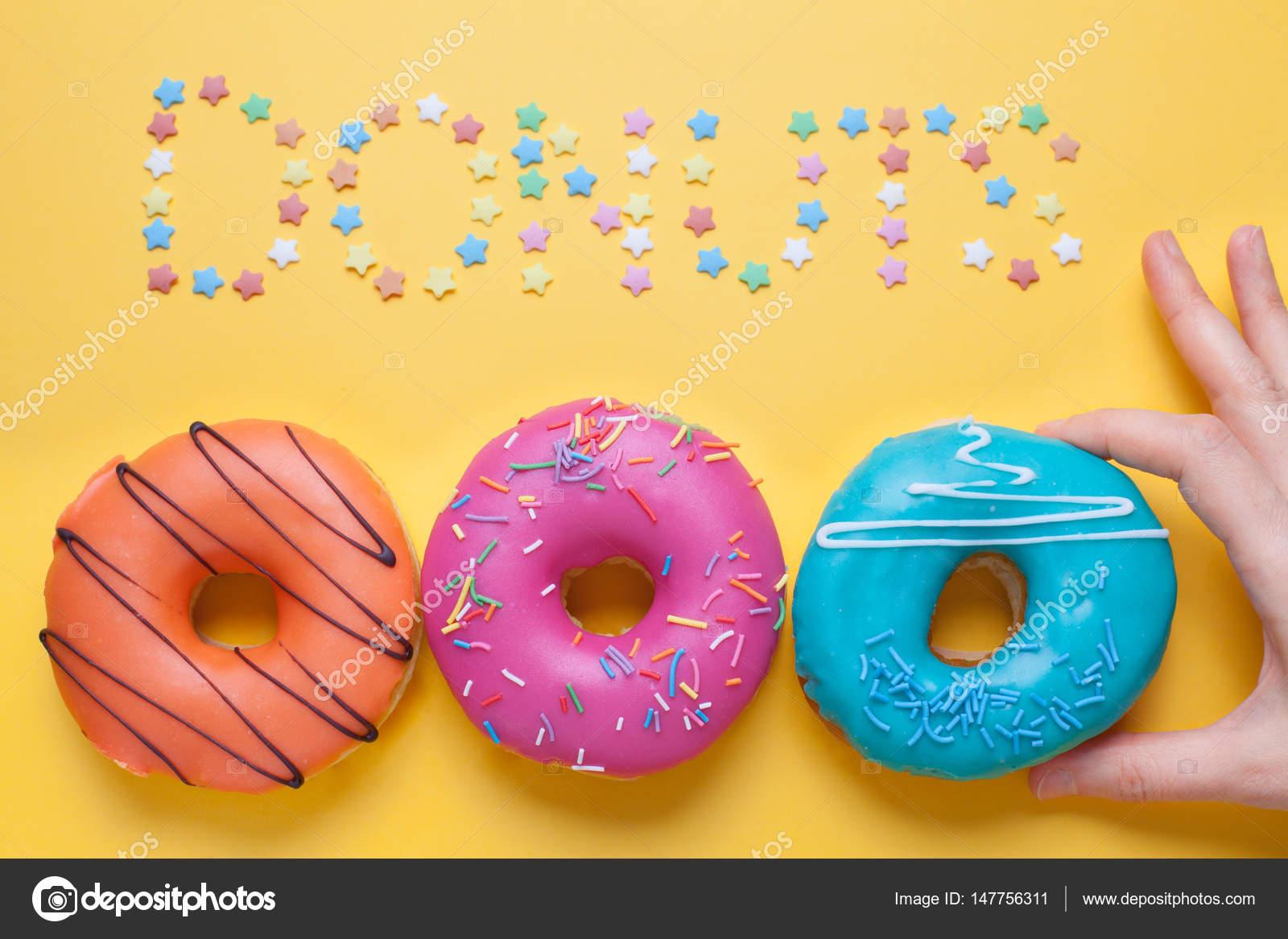 Eine weibliche Hand nimmt einen blauen Donut in der Glasur. Rosa und ...