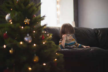 Little long-haired boy is watching a video on the phone sitting on the couch by the Christmas tree. A child playing on the phone for the new year