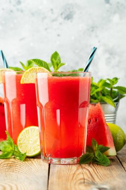 Watermelon slushie with lime and mint, summer refreshing drink in tall glasses on a light blue background. Sweet cold smoothie.