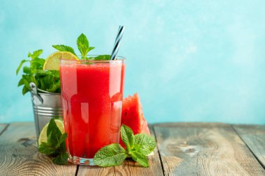 Watermelon slushie with lime and mint, summer refreshing drink in tall glasses on a light blue background. Sweet cold smoothie with copy space.