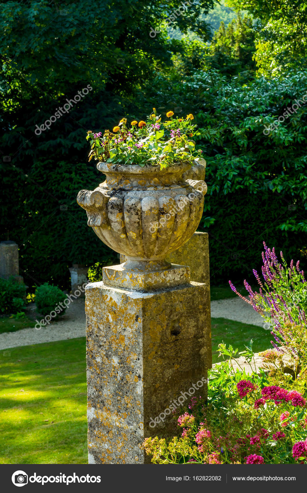 Depositphotos & Concrete flower pots in the garden on a pedestal stylized antiqu ...