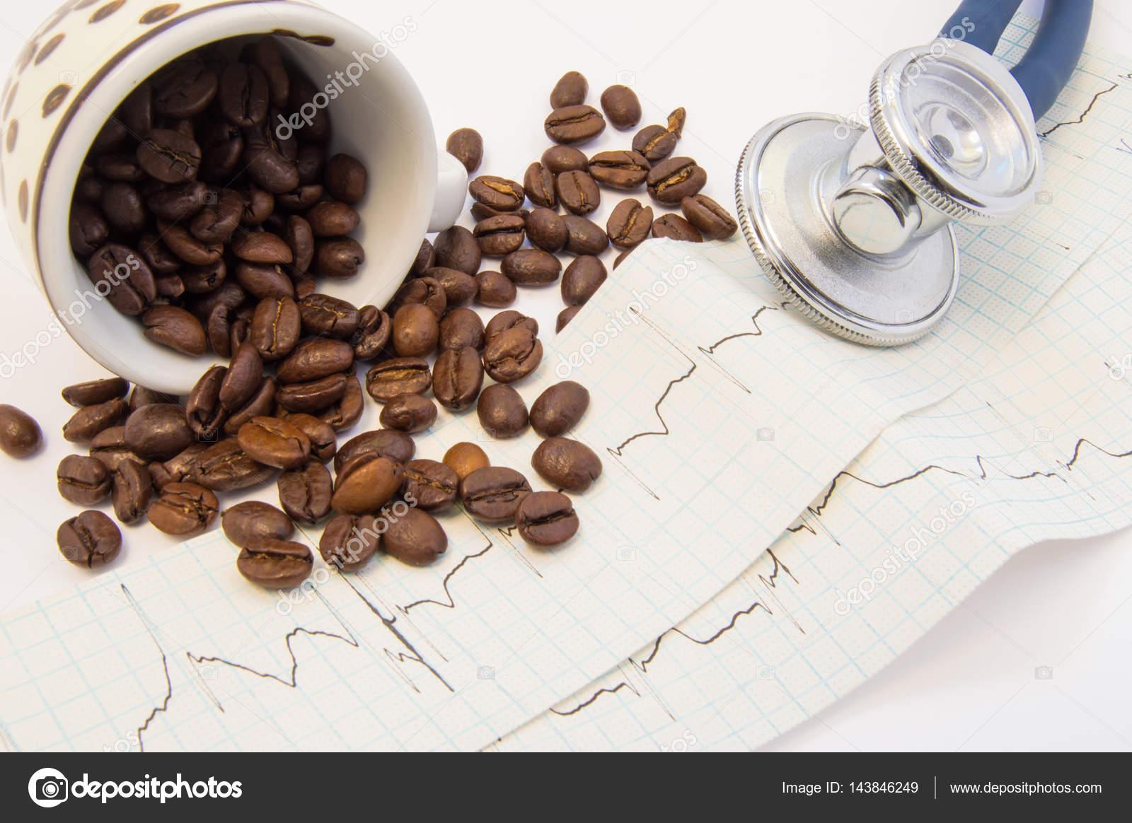 Kaffeebohnen von c verschüttet und verstreut auf dem Papier EKG in ...