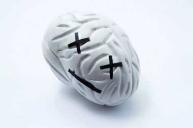 Concept photo of death, critical injury, damage or dead human brain. Model of brain with emotion dead smile symbolizes serious disease, death or failure of function in coma, stroke, edema, dementia