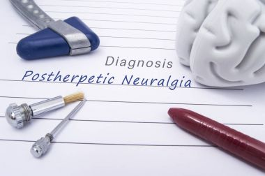 Figure of human brain, blue neurological reflex hammer, neurological needle and brush for test sensitivity and ballpoint pen lie on paper form with a medical diagnosis of Postherpetic Neuralgia (PHN)
