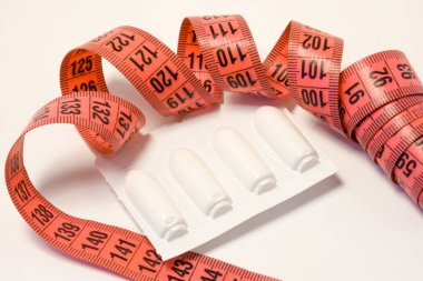 Laxatives rectal suppositories in package and measuring tape around. Using laxatives medicines for weight loss and treating obesity concept photo. Alternative pharmacological methods to weight loss