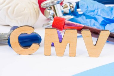 CMV abbreviation or acronym in foreground, in laboratory, scientific or medical practice meaning Cytomegalovirus, with model of brain, neurological hammer, laboratory test tubes,  stethoscope
