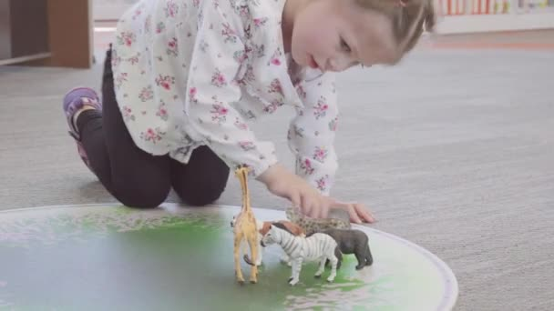 Little girl with toys on interactive mat at the local library
