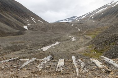 Old wooden logs, used for the coal mining industry, in the landscape of glacial moraine rocks in Longyear valley, Svalbard. Arctic landscape.