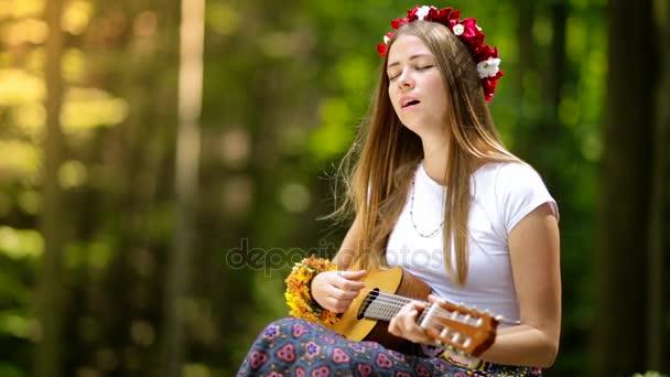 Romantická dívka v věnec z divoce rostoucích květin, cestuje se svou kytarou. Léto