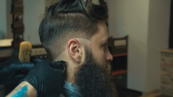 Unparalleled Barber With A Beard And A Tattoo Is Cutting The Hair Of His Client In The Barbershop He Is Using A Cutting Comb And A Hair Clipper
