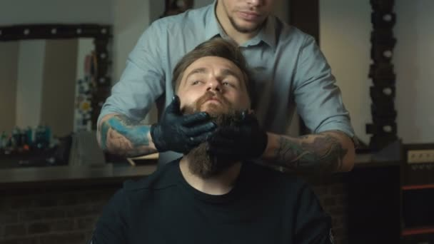 Handsome man with a long beard and undercut in barbershop