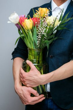 A young guy in a business suit in a studio with a bouquet of tulips.