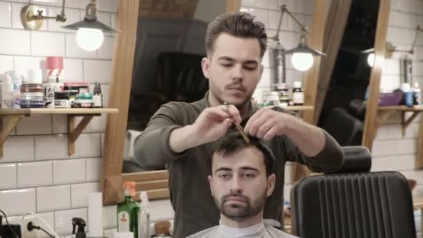 Man hairdresser doing haircut beard adult men in the mens hair salon. Haircut with scissors