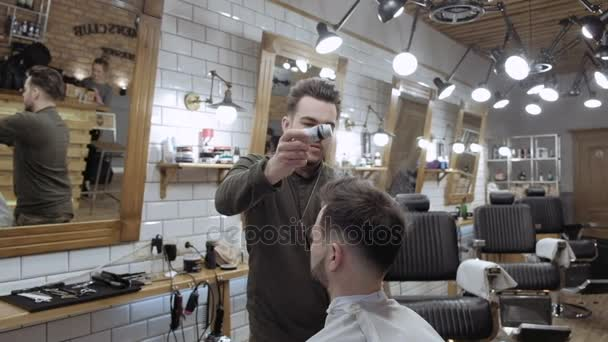 Handsome bearded man is smiling while having his hair cut by hairdresser at the barbershop