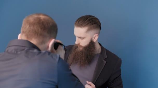 Fotograf für Mann-Modell im Studio mit blauem Hintergrund zu fotografieren. Guy-Modell mit langem Bart. Fashion Katalog schießen. Porträt, Nahaufnahme