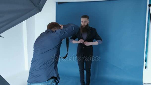 Fotograf für Mann-Modell im Studio mit blauem Hintergrund zu fotografieren. Guy-Modell mit langem Bart. Fashion Katalog Shooting